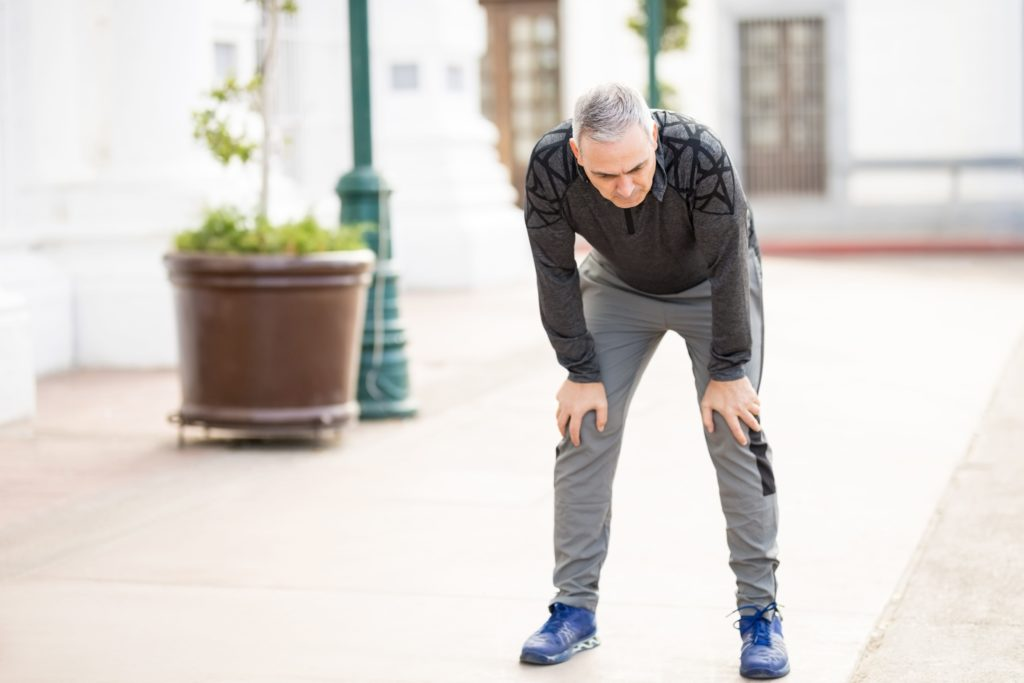 Photo of a man with gray hair recovering after a run.
