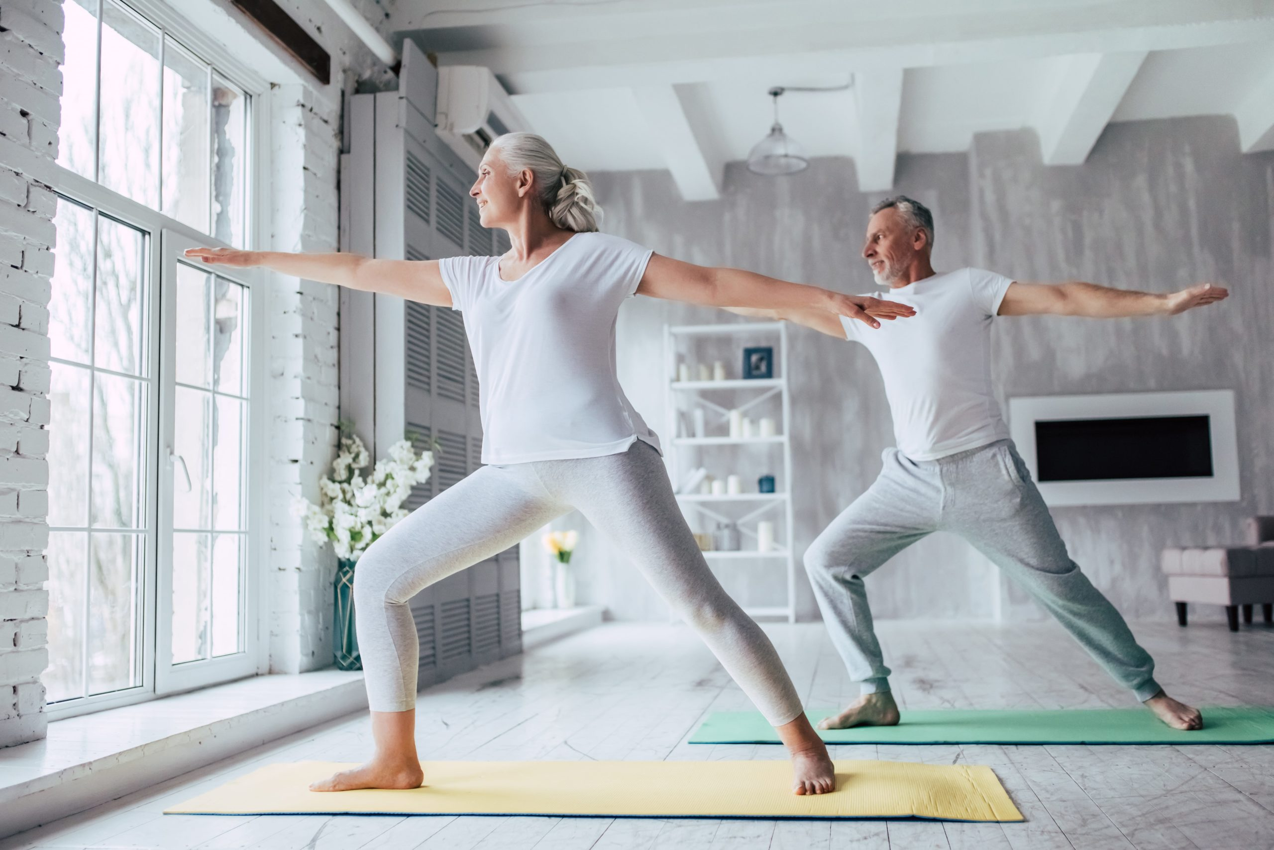 Photo of a healthy older couple doing yoga at home.